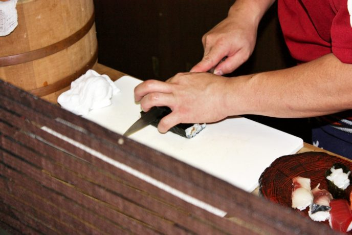 寿司を包丁で切る
